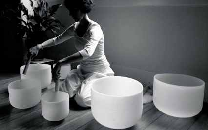 A sound therapist playing crystal singing bowls